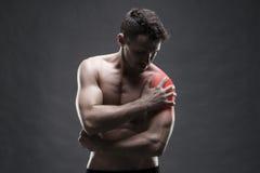 плечо боли мужчина тела мышечный Красивый культурист представляя на серой предпосылке Стоковые Изображения RF