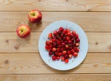 Плита вишен и красных яблок на деревянном столе Стоковые Фотографии RF