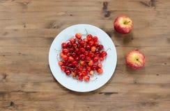 Плита вишен и красных яблок на деревянном столе Стоковая Фотография RF