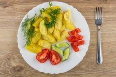 Плита зажаренных картошек, овощей, зеленых цветов и вилки на таблице Стоковая Фотография