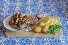 Плита зажаренных прибалтийских сельдей, картошки, лимона, красного лука и равенств Стоковые Изображения