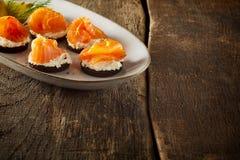 Плита канапе копченых семг на деревенской таблице Стоковые Изображения