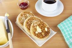 Плита масла облила crumpets и черный кофе Стоковая Фотография