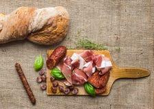 Плита мяса на деревенской деревянной доске над грубым backgroun дерюги Стоковое Изображение