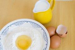 Плита при мука, яичка и кувшин молока стоя на предпосылке стоковые изображения rf