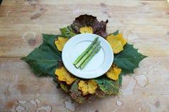 Плита при сырцовые копья спаржи окруженные листьями стоковая фотография rf