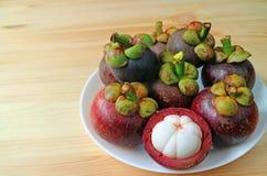 Плита плодоовощей зрелого фиолетового мангустана всех и раскрытая для того чтобы показать привлекательное чисто белое мясо на дер Стоковые Фотографии RF