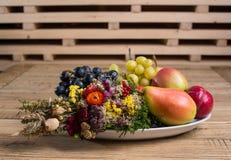 Плита плодоовощ с украшениями полевого цветка на деревянной таблице Стоковые Фотографии RF