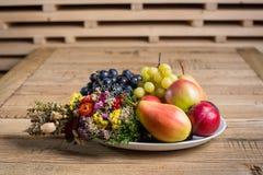 Плита плодоовощ с украшениями полевого цветка на деревянной таблице Стоковые Изображения RF