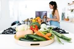 Плита свежих овощей и красивой молодой женщины варя в t Стоковая Фотография