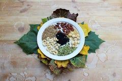 Плита смешанных гаек и семян окруженных листьями осени стоковые фотографии rf
