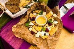 Плита сыра с полениками и медом стоковая фотография