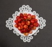 Плита с вишнями на кружевной салфетке на серой предпосылке, осматривает сверху Стоковое Изображение