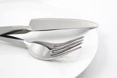 Плита с вилкой и изолированный нож Стоковые Фото