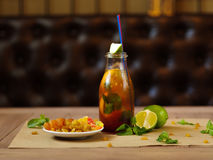 Плита с изюминками и высушенными абрикосами, коктеилем с лимоном, коктеилем, сочными кусками известки на запачканном свете Стоковая Фотография