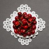 Плита с красными вишнями на кружевной салфетке на серой предпосылке, взгляд сверху Стоковые Фото