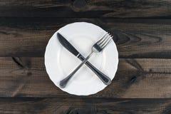 Плита с пересеченным ножом вилки и масла Стоковая Фотография