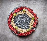 Плита с различными красочными ягодами на серой каменной предпосылке, взгляд сверху Стоковое фото RF