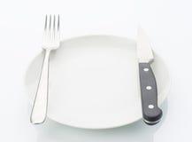 Плита фарфора с ножом и вилка изолированная на белизне стоковое изображение