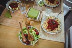 Плиты салата и макаронных изделий на dinning таблице Стоковое Фото