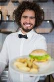 Плиты сервировки кельнера картофельной стружки и бургера в баре Стоковое фото RF