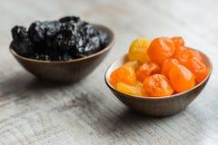 2 плиты с высушенными плодоовощами на деревянной предпосылке: высушенные мандарины и черносливы Стоковые Изображения RF