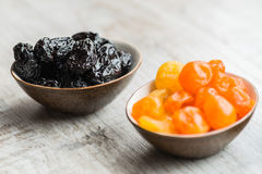 2 плиты с высушенными плодоовощами на деревянной предпосылке: высушенные мандарины и черносливы Стоковое Изображение RF