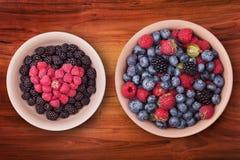 Плиты с ягодами на деревянном столе Стоковое Изображение RF