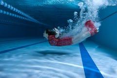 Пловец в платье ныряет под водой стоковые фотографии rf