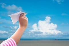 Плоская бумага в руке детей над небом seaand голубым Стоковые Фотографии RF