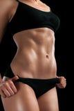 Плоская девушка tummy на черноте Стоковая Фотография
