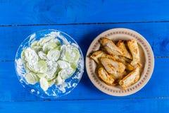 Плоская жареная курица положения с салатом огурца над голубой деревянной предпосылкой планок Стоковые Фотографии RF