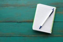 Плоский взгляд положения блокнота и ручки на деревянном столе Стоковые Изображения RF