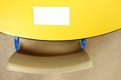 Плоский взгляд положения пустого белого примечания на желтой таблице Стоковое фото RF
