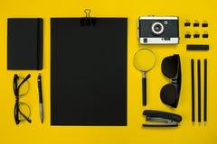 Плоский дисплей положения устройств офиса с блокнотом, винтажной камерой, ручкой, превращается, стекла и etc Взгляд сверху черный Стоковое Изображение