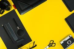 Плоский дисплей положения устройств офиса с блокнотом, винтажной камерой, ручкой, превращается, стекла и etc Взгляд сверху черный Стоковая Фотография