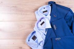 Плоский комплект положения одежд классических людей как голубой костюм, рубашки, коричневые ботинки, пояс и связь на деревянной п Стоковое Изображение RF