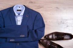 Плоский комплект положения одежд классических людей как голубой костюм, рубашки, коричневые ботинки, пояс и связь на деревянной п Стоковое фото RF