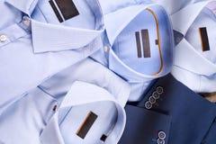 Плоский комплект положения одежд классических людей как голубой костюм, рубашки, коричневые ботинки, пояс и связь на деревянной п Стоковые Фото