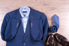 Плоский комплект положения одежд классических людей как голубой костюм, рубашки, коричневые ботинки, пояс и связь на деревянной п Стоковое Изображение