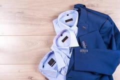 Плоский комплект положения одежд классических людей как голубой костюм, рубашки, коричневые ботинки, пояс и связь на деревянной п Стоковые Изображения RF