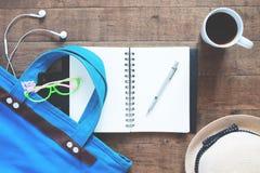 Плоский комплект положения тетради, ручка, аксессуары девушки и чашка кофе, взгляд сверху на древесине Стоковое Фото