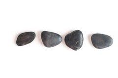 Плоский округленный камень 4 лежа на белой предпосылке Стоковая Фотография RF