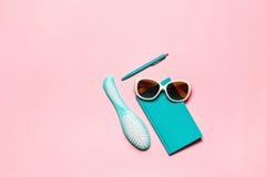 Плоский minimalistic женственный состав аксессуара бирюзы: щетка для волос, стекла, дневник и ручка изолированные на розовом экзе Стоковое Изображение RF
