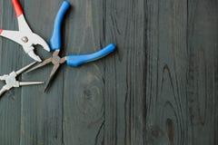 Плоскогубцы на черное деревянном Стоковые Фото