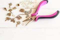 Плоскогубцы, цепь, кольца металла и шкентели на белой деревянной предпосылке Как сделать браслет металла Стоковая Фотография