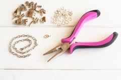 Плоскогубцы, цепь, кольца металла и шкентели на белой деревянной предпосылке Как сделать браслет металла Стоковые Фотографии RF
