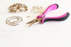 Плоскогубцы, цепь, кольца металла и шкентели на деревянной предпосылке Как сделать браслет металла шаг Стоковые Изображения