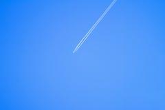 Плоское летание в ясном голубом небе и белом следе от полета Стоковое Изображение RF