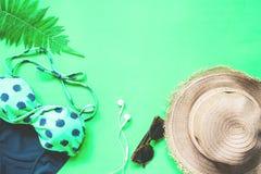 Плоское положение бикини и аксессуаров с папоротником выходит на зеленую предпосылку, лето и тропическую концепцию Стоковая Фотография RF